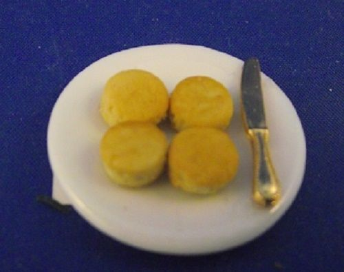 4 scones on a plate with knife