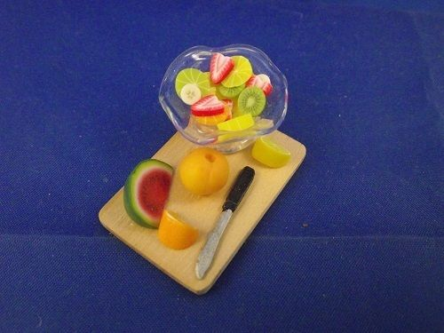 Board with fruit slice and fruit and a Knife Fruit Cocktail