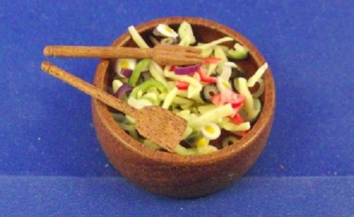 Brown bowl with chopped salad and wooden severs